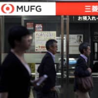 A woman uses an ATM inside a branch of MUFG Bank Ltd. | BLOOMBERG