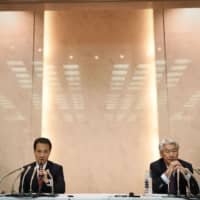 Kentaro Okuda (left), incoming chief executive officer of Nomura Holdings Inc., holds a news conference with his predecessor, Koji Nagai, in Tokyo on Monday. | BLOOMBERG
