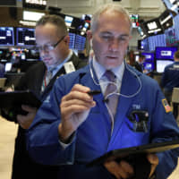 Traders Robert Arciero (left) and Timothy Nick work on the floor of the New York Stock Exchange Wednesday. Stocks are opening broadly higher as traders became more hopeful that a trade deal between the U.S. and China was making progress. | AP