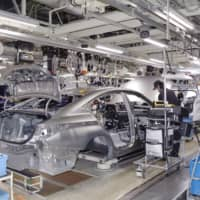 Workers build cars at Toyota Motor Corp.'s plant in Fukuoka Prefecture. Dogged by China's economic slowdown and the October consumption tax hike, business sentiment among large Japanese companies fell to its lowest level in three years in the October-December quarter. | KYODO