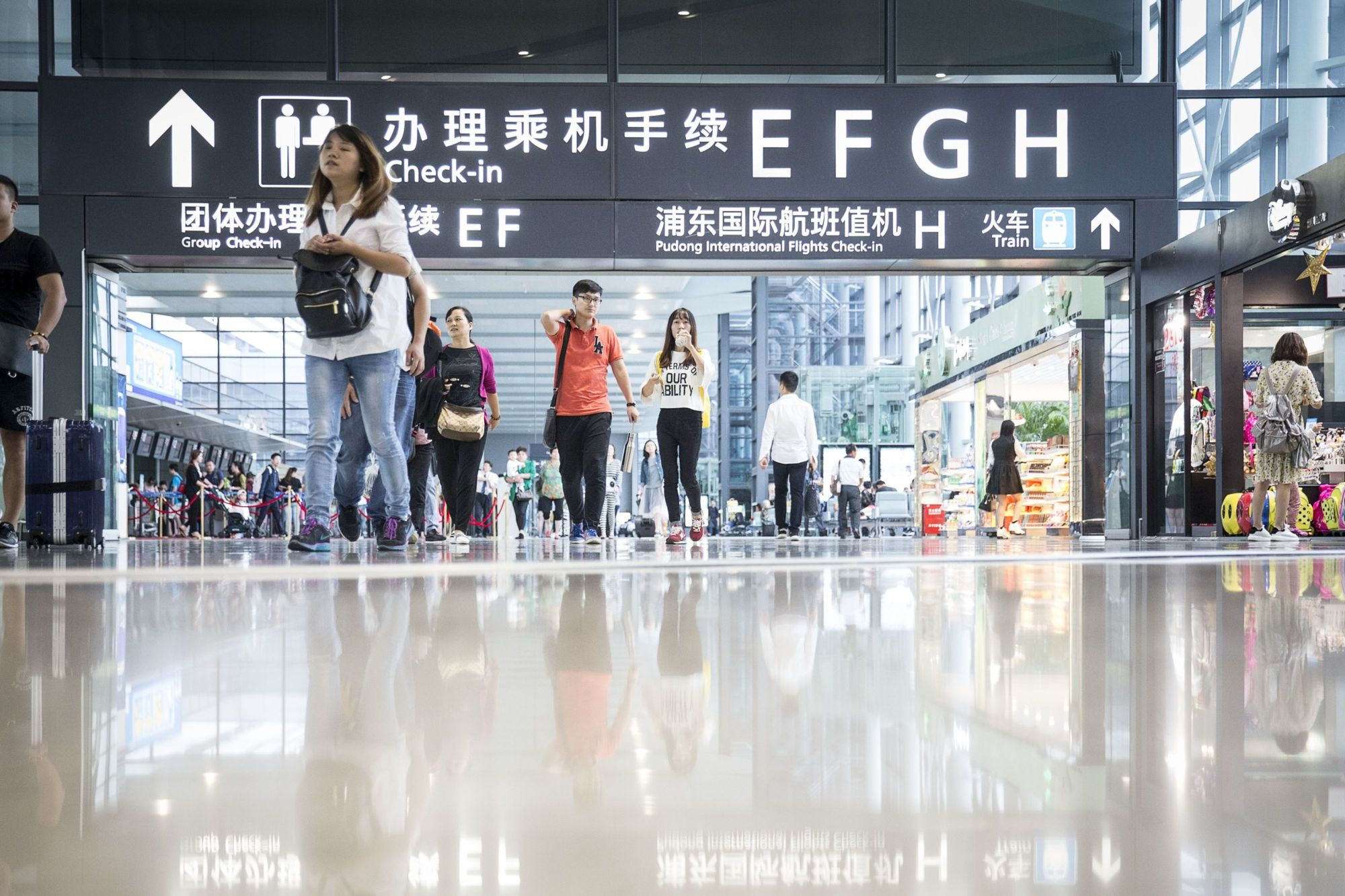 Travelers walk through Shanghai's Hongqiao Airport. The Japanese and Chinese governments are reportedly discussing an increase in the number of flights linking Shanghai and Japanese cities to alleviate congestion and improve security. | BLOOMBERG