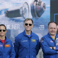 NASA astronaut Nicole Mann (left), Boeing astronaut Chris Ferguson (center) and NASA astronaut Mike Fincke stand in front of the countdown clock during a press conference at the Kennedy Space Center, in Cape Canaveral, Florida, Thursday. They will be the first crew to fly on the Starliner spacecraft some time next year. | AP
