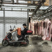 A man sits on a motorcycle at a pork wholesale market on the outskirts of Shanghai. China has cut import tariffs on a wide range of goods including pork, consumer and technology items. | BLOOMBERG