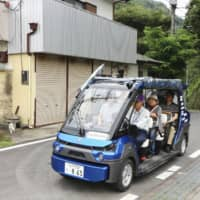 A community vehicle goes on a trial run in Hitachiota, Ibaraki Prefecture, in July. | KYODO