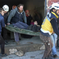 Civil Defense workers evacuate an injured man from the site of airstrikes in the village of Deir Sharqi, in Idlib province, Syria, Tuesday. | SYRIAN CIVIL DEFENSE WHITE HELMETS / VIA AP