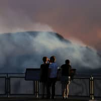 Smoke from the Green Wattle Creek fire is seen from Echo Point lookout in Katoomba, New South Wales, on Friday. | AAP / VIA REUTERS