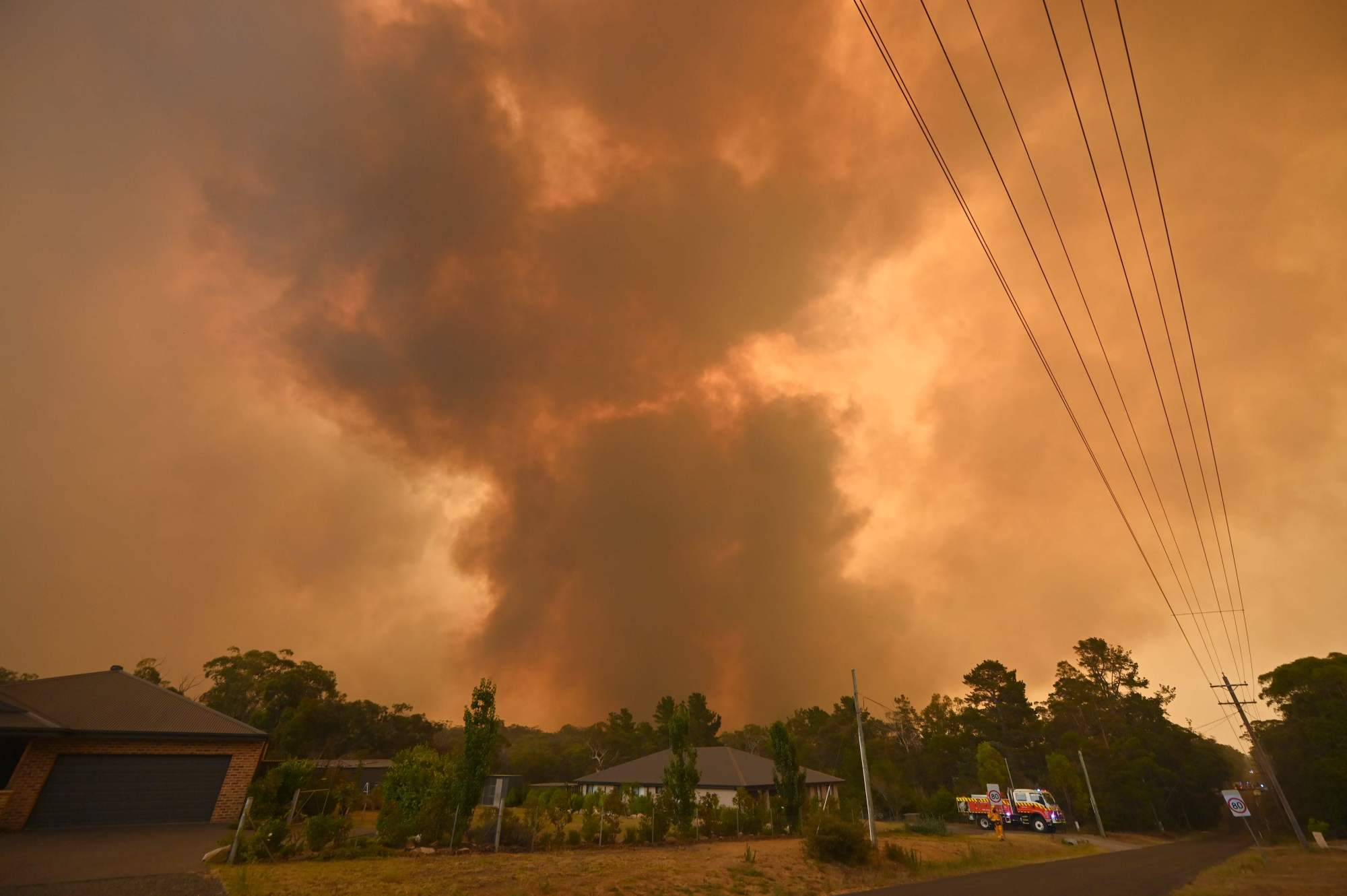 A large bushfire burns near houses in Bargo, southwest of Sydney, on Saturday. | AFP-JIJI