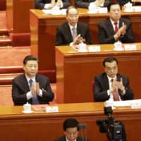 Chinese President Xi Jinping applauds during the closing of the Second Session of the 13th National People's Congress at the Great Hall of the People in Beijing on March 15. Xi has repeatedly called for training more capable cadres, and the Communist Party's Central Committee vowed in March to accelerate that by promoting the exchange of officials across local areas, departments and state-owned enterprises. | BLOOMBERG
