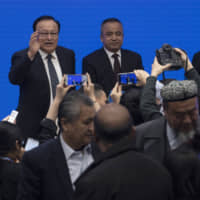 Shohrat Zakir, chairman of China's Xinjiang Uighur Autonomous Region, left reacts to journalists as he leaves after a news conference in Beijing on Monday. | AP