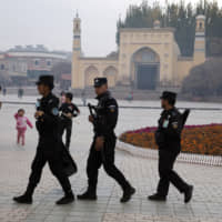 Uighur security personnel patrol near the Id Kah Mosque in Kashgar, in western China's Xinjiang region, on Nov. 4, 2017. | AP