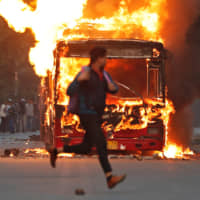 A man runs past a burning bus that was set on fire by demonstrators during a protest against a new citizenship law in New Delhi on Sunday. | REUTERS