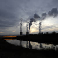 Smoke rises from chimneys of the Turow power plant located close to the Turow lignite coal mine near the town of Bogatynia, Poland, in November. | AP