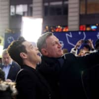 Actors Daniel Craig and Rami Malek pose for a selfie during a promotional appearance on TV in Times Square for the new James Bond movie 'No Time to Die' in the Manhattan borough of New York City Wednesday. | REUTERS