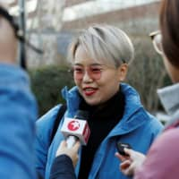 Teresa Xu, 31, talks to journalists outside Chaoyang People's Court before a court hearing regarding her suit against a Beijing hospital over its rejection of her request to freeze her eggs, on the grounds that she is unmarried, in Beijing on Monday. | REUTERS