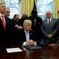 Faith leaders place their hands on the shoulders of U.S. President Donald Trump as he takes part in a prayer for those affected by Hurricane Harvey in the Oval Office of the White House in Washington in 2017. | REUTERS