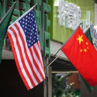 The U.S. and Chinese flags fly displayed outside a hotel in Beijing in May. The United States secretly expelled two Chinese Embassy officials in September after they drove onto a sensitive military base in Virginia, The New York Times reported Sunday. The newspaper, which cited people with knowledge of the episode, said it appeared to be the first time in more than 30 years that the U.S. has expelled Chinese diplomats on suspicion of espionage. | AFP-JIJI