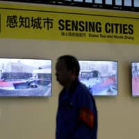 A man walks past the 'Eyes of the City' exhibition, part of the joint Hong Kong/Shenzhen Biennale of Urbanism and Architecture, at Futian Station in Shenzhen, China, on Monday. | REUTERS