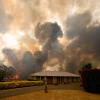 A bushfire burns behind a property in Balmoral, 150 km southwest of Sydney, on Thursday. | AFP-JIJI