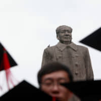 A statue of the late Chinese leader Mao Zedong overlooks a graduation ceremony at Fudan University in Shanghai. | REUTERS