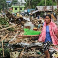 A resident walks past debris from destroyed houses after Typhoon Kammuri hit the city of Sorsogon, south of of Manila, on Tuesday. | AFP-JIJI