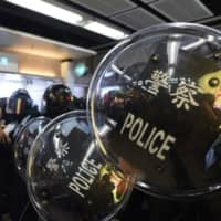 Police stand guard during a protest at the New Town Plaza shopping mall in Shatin in Hong Kong on Sunday. | AFP-JIJI