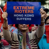Government supporters hold placards during a rally at Harbour Road Garden in the Wan Chai district of Hong Kong on Saturday. | BLOOMBERG
