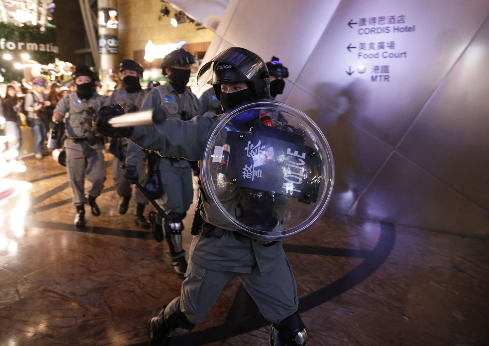 Riot police hold back anti-government protesters at a shopping mall in Hong Kong on Thursday.   REUTERS