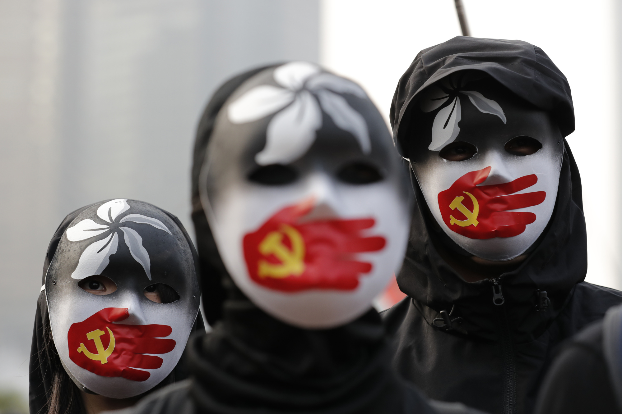 People wearing masks stand during a rally to show support for Uighurs and their fight for human rights in Hong Kong on Sunday. | AP