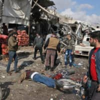 Bodies lie on the ground following a regime airstrike Monday on a market in the town of Maaret al-Numan in the jihadi-run Syrian province of Idlib. | AFP-JIJI