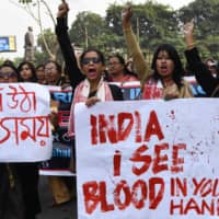 Demonstrators hold placards and shout slogans during a protest against India's new citizenship law in the city of Guwahati on Saturday. | AFP-JIJI