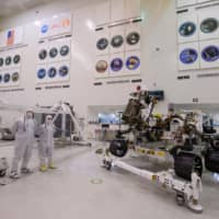The Mars 2020 Rover is seen in the spacecraft assembly area clean room Friday during a media tour at NASA's Jet Propulsion Laboratory in Pasadena, California. The Mars 2020 rover, which will take off in a few months to the Red Planet, will not only search for possible traces of past life, it will also serve as a 'precursor to a human mission to Mars,' NASA scientists said when presenting the spacecraft to the press. | AFP-JIJI