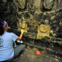An archaeologist works cleaning the stucco of the Temple of the U, located in the archaelogy area of Kuluba, in Tizimin, Yucatan state, Mexico, in this photo released Tuesday. | NATIONAL INSTITUTE OF ANTHROPOLOGY AND HISTORY / HANDOUT / VIA REUTERS