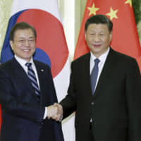 South Korean President Moon Jae-in (left)and Chinese President Xi Jinping appear Monday ahead of their meeting at the Great Hall of the People in Beijing. | YONHAP / VIA AFP-JIJI