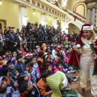 Bolivian interin President Jeanine Anez is dressed as Santa Claus during a Christmas celebration at the Quemado presidential palace in La Paz Tuesday. | BOLIVIA'S PRESIDENTIAL MINISTRY OFFICIAL TWITTER ACCOUNT @MINPRESIDENCIA / VIA AFP-JIJI