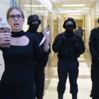 Russian opposition activist Lyubov Sobol reports live by phone as policemen stand guard at the Foundation for Fighting Corruption office in Moscow Thursday. Russian opposition leader Alexei Navalny, the most prominent foe of President Vladimir Putin and the governing United Russia party, was detained in his office in Moscow. | AP