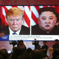 A large display screen shows North Korean leader Kim Jong Un and U.S. President Donald Trump during a symposium in Seoul in June. | AP