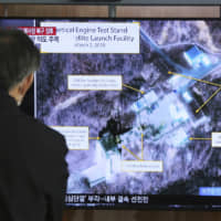 A man watches a TV screen showing an image of the Sohae Satellite Launching Station in Tongchang-ri, North Korea, during a news program in Seoul in March. | AP