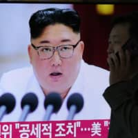 A man walks past a television news program showing pictures of North Korean leader Kim Jong Un, at a railway station in Seoul on Monday. | AFP-JIJI
