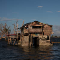 A bamboo hut sits on top of concrete structures in the submerged coastal village of Sitio Pariahan, Bulakan, Bulacan, north of Manila on Nov. 25. | REUTERS