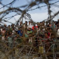 Rohingya refugees gather in the 'no man's land' behind Myanmar's border lined with barb wire fences in the Maungdaw district, Rakhine state, bounded by Bangladesh last year. | AFP-JIJI