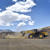 A front-end loader is used to reinforce a safety berm inside the open pit at a rare earth facility in California in June 2015. | REUTERS