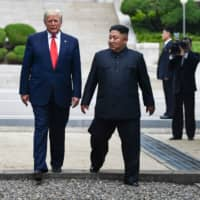 North Korean leader Kim Jong Un and U.S. President Donald Trump cross south of the Military Demarcation Line that divides North and South Korea, after Trump briefly stepped over to the northern side, in the Joint Security Area of Panmunjom at the Demilitarized Zone on June 30. | AFP-JIJI