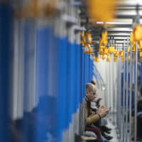 A man uses his smartphone in a subway train in Moscow Monday. Russia's Communications Ministry has scheduled an exercise for Monday that is intended to simulate what is being called the isolated operation of the internet. | AP