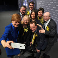 Scottish First Minister Nicola Sturgeon (left) takes a selfie with her Glasgow politicians at the count center in Glasgow on Friday after results had been declared in Thursday's U.K. general election. | AFP-JIJI
