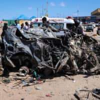 The wreckage of a vehicle that was destroyed during a bomb attack is seen at a Mogadishu checkpoint on Saturday. | AFP-JIJI