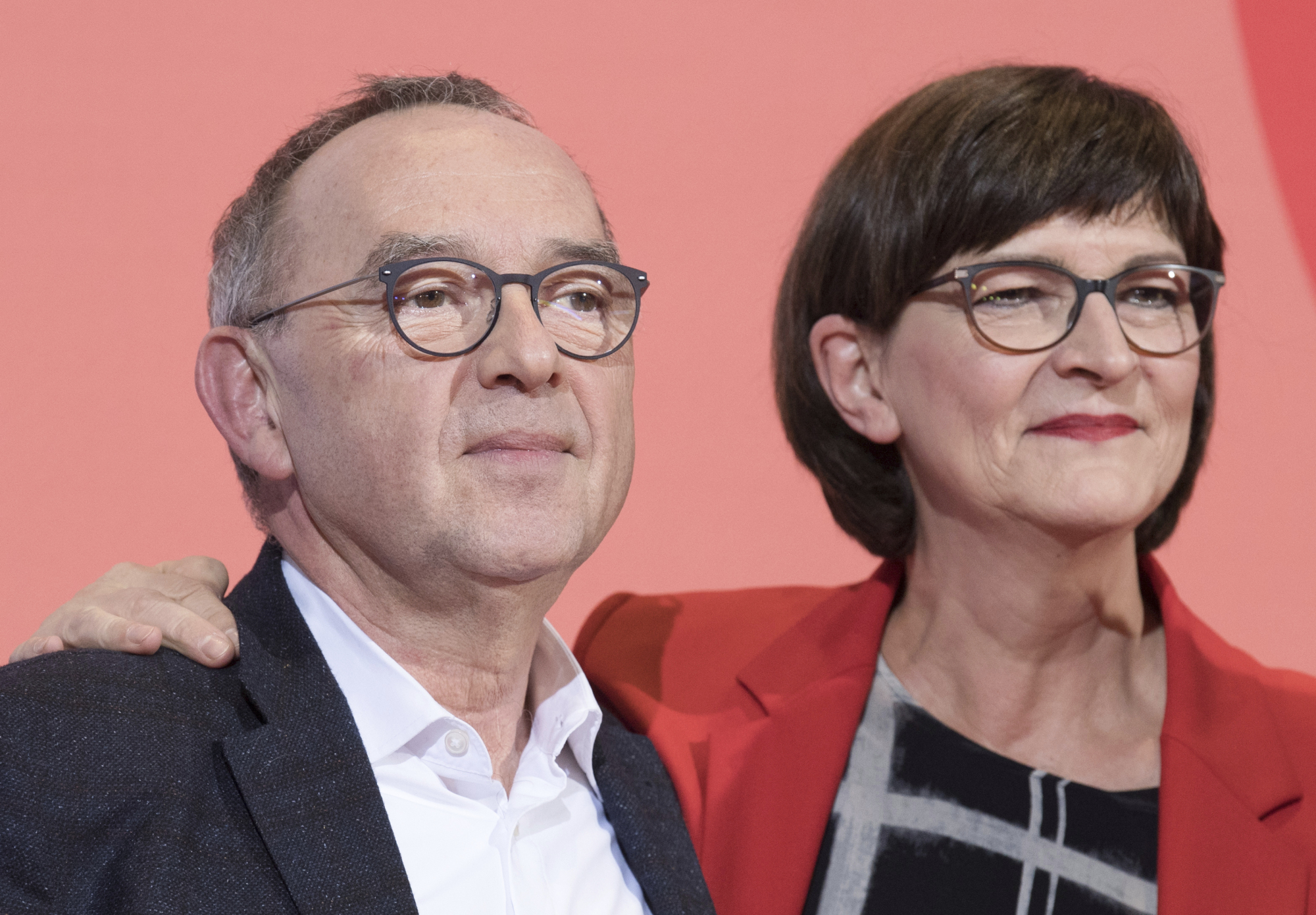Norbert Walter-Borjans and Saskia Esken stand on the podium after winning the Social Democratic Party chairmanship at the party's headquarters in Berlin on Saturday. | AP