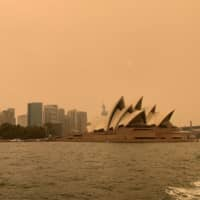 Haze from wildfires obscures the sun setting above the Sydney Opera House on Dec. 6. | REUTERS