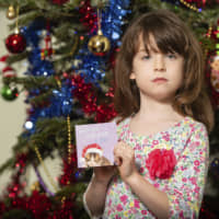 Florence Widdicombe, 6, poses with a Tesco Christmas card from the same pack as the one containing a message from a Chinese prisoner, in London on Sunday. The U.K.-based grocery chain has halted production at a factory in China after a British newspaper said it used forced labor to produce charity Christmas cards. | AP