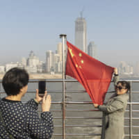 A passenger holds a Chinese flag while crossing the Yangtze River by ferry in Wuhan, China, on Dec. 11. | BLOOMBERG