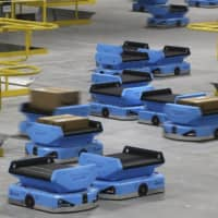 Amazon and its rivals are increasingly requiring warehouse employees to get used to working with robots. The company now has more than 200,000 robotic vehicles it calls 'drives' that are moving goods through its delivery-fulfillment centers around the U.S. | AP